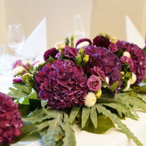 fioletowa kompozycja kwiatowa na stole młodej pary