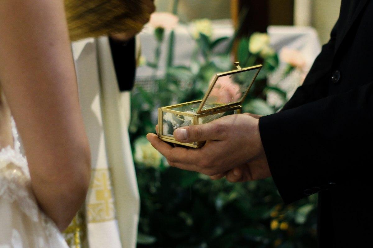 Zdjęcie pary młodej trzymającej szkatułkę z obrączkami