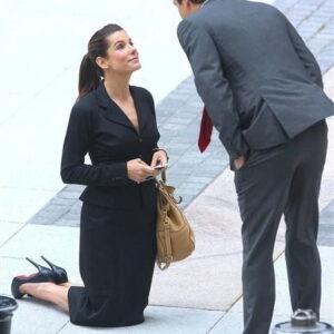 kobieta klęczy na środku ulicy